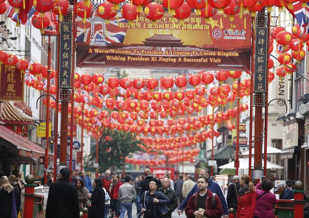 People walk through a decorated street in Chinatown, London, Friday, Oct. 16, 2015