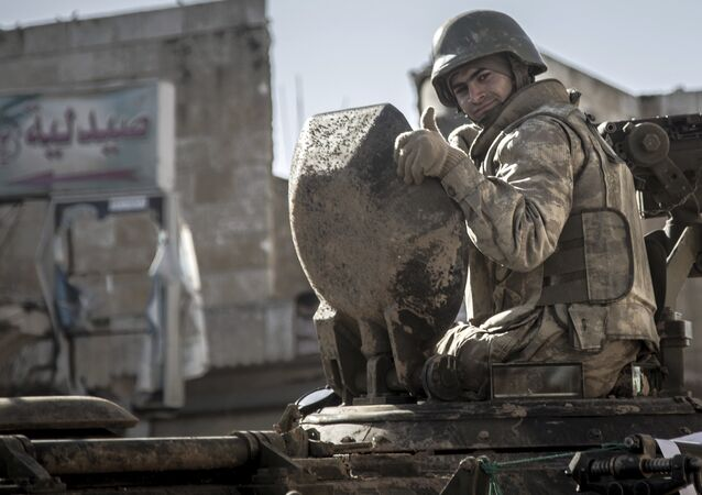 In this February 22, 2015, file photo, a soldier gives the thumbs up as Turkish army's armored vehicles and tanks roll in Syrian town of Ayn al-Arab, also known as Kobani, as they return from the Ottoman tomb in Syria.
