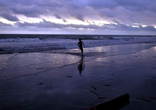 A young boy plays at sunset on the beach of Kerema, Papua New Guinea, on September 9, 2014