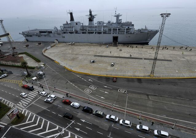 British soldiers board the Royal Navy warship HMS Albion, background, at Santander's port, northern Spain, on Tuesday, April 20, 2010. The warship came to take back to England nearly 800 British soldiers and civilians stranded by the volcanic ash cloud.
