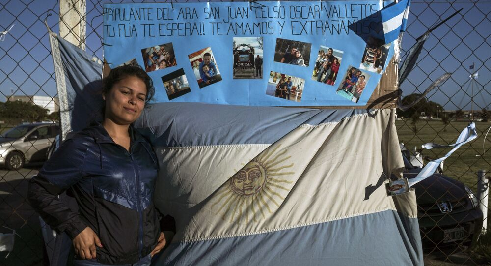 Malvina Vallejos, sister of missing submariner Celso Oscar Vallejos poses next to a supportive message for the 44 crew members of Argentine missing submarine outside Argentina's Navy base in Mar del Plata, on the Atlantic coast south of Buenos Aires, on November 21
