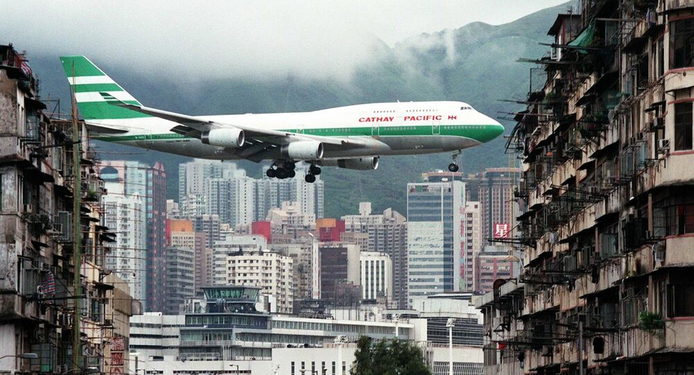 Hong Kong flag carrier Cathay Pacific, Boeing 747-400 jumbo jet, flies over the Kai Tak Airport control tower bottom as it approaches the Runway 13 on the last day of the 73-year-old airport