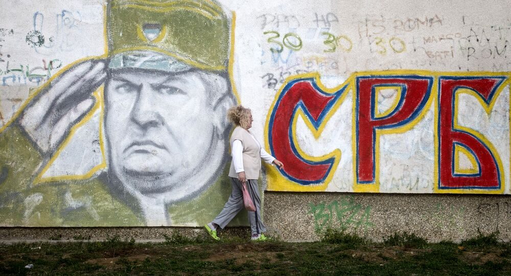 A woman walks past a graffiti depicting former Bosnian Serb commander Ratko Mladic and reading Serbia written in Cyrillic, painted on a wall in Belgrade on Nocember 22, 2017.