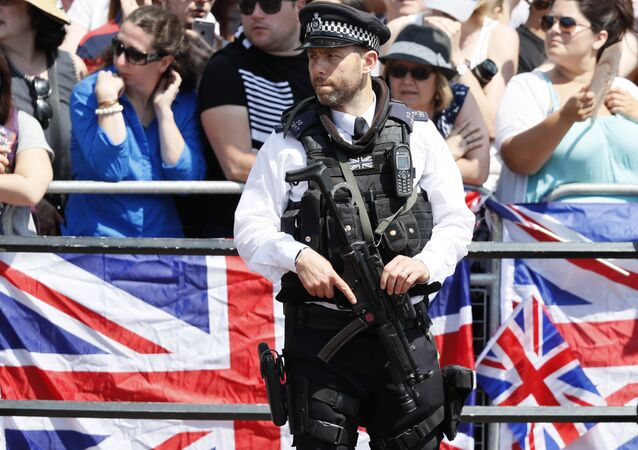 An armed police officer keeps guard as Britain's Royals return to Buckingham Palace, after attending the annual Trooping the Colour Ceremony in London, Saturday, June 17, 2017.