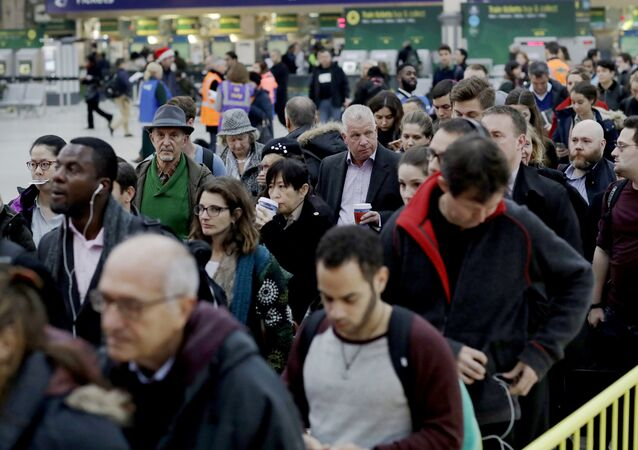 Passengers queue up for an express train in Victoria rail station London, Tuesday, Dec. 13, 2016.
