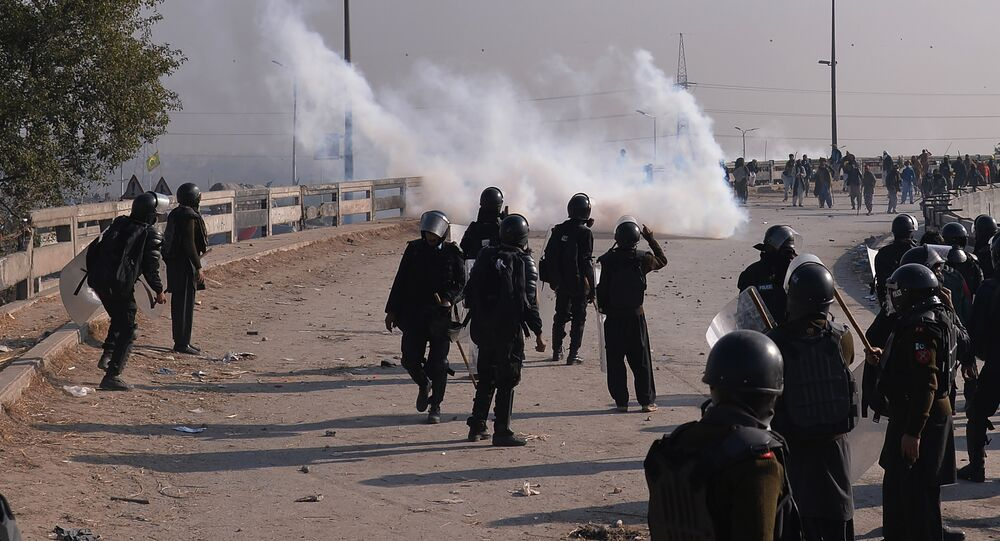 Pakistani riot policemen face off with protesters of the Tehreek-i-Labaik Yah Rasool Allah Pakistan (TLYRAP) religious group during a clash in Islamabad on November 25, 2017