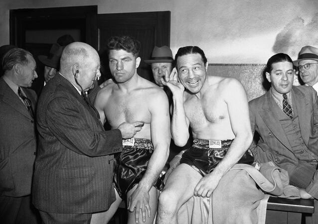 Clowning Max Baer cups his ear