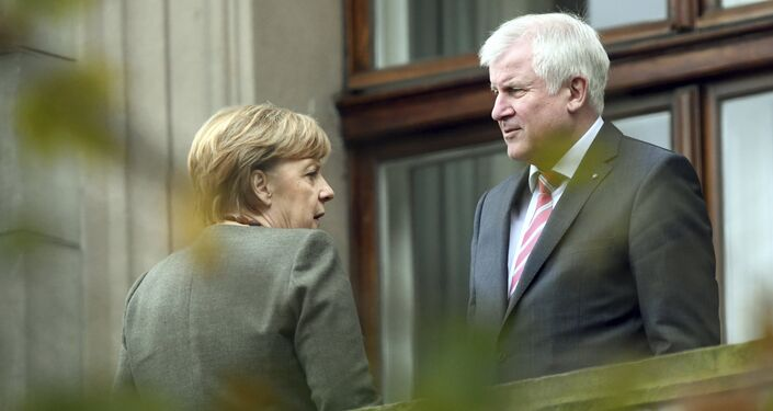 Chancellor Angela Merkel, left, talks to Bavarian governor Horst Seehofer during talks on forming a new government in Berlin Thursday, Oct. 26 2017