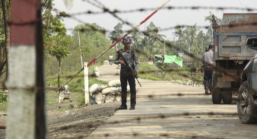A Myanmar police officer stands watch as journalists arrive in Shwe Zar village in the suburb of Maungdaw town, northern Rakhine state of Myanmar, on Wednesday, Sept. 6, 2017