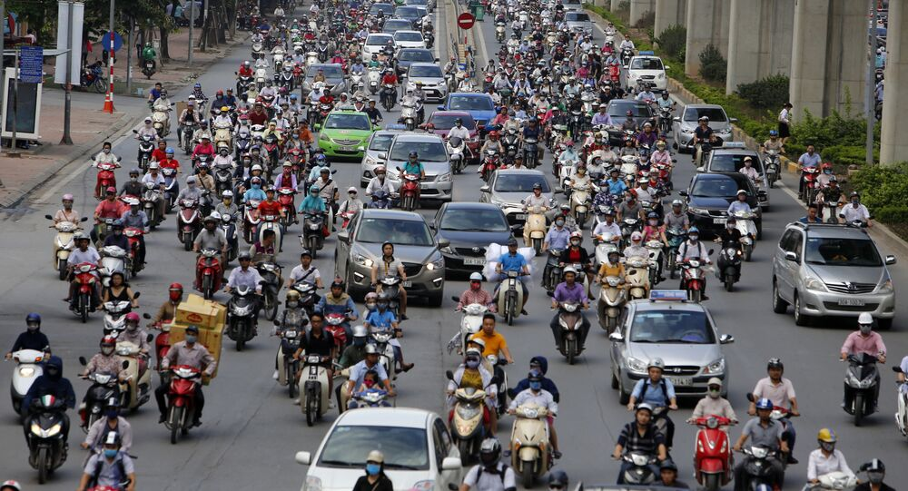 In this June 21, 2017, photo, motorbikes and cars fight for space on a street in Hanoi, Vietnam