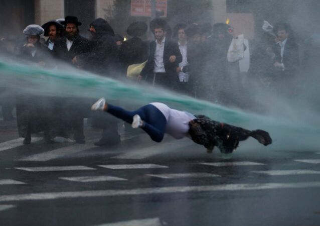 A bystander falls as Israeli police spray water during a demonstration by ultra-Orthodox Jews against the detention of members of their community who failed to report to a military recruiting office, in Jerusalem November 26, 2017