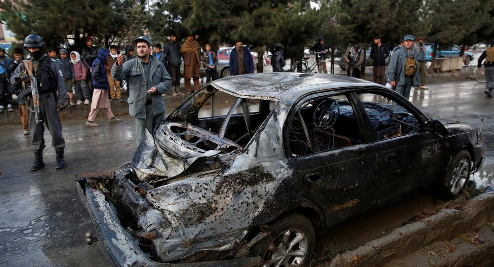 People look on at a damaged vehicle after a suicide bomb attack in Kabul, Afghanistan November 16, 2017