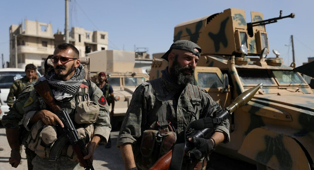 A fighter of the Syrian Democratic Forces (SDF) carries a weapon as he stands near a military vehicle in Raqqa, Syria, October 16, 2017