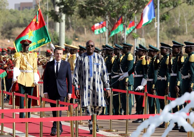 Burkina Faso's President Roch Marc Christian Kabore and French President Emmanuel Macron review troops during a welcoming ceremony at the Presidential Palace in Ouagadougou, Burkina Faso