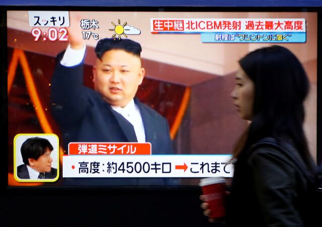 A woman walks past a street monitor showing North Korea's leader Kim Jong Un in a news report about North Korea's missile launch, in Tokyo, Japan, November 29, 2017