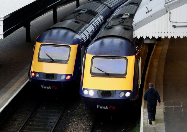 A worker passes First Great Western trains at Paddington Station in London November 21, 2010.