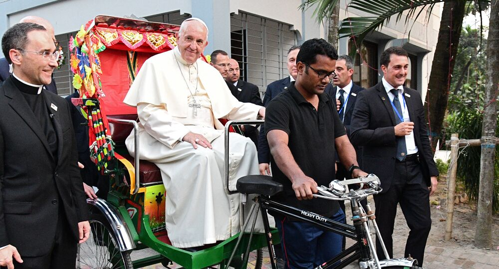Pope Francis takes a ride in a rickshaw during the second day of his visit to Bangladesh, in Dhaka on December 1, 2017