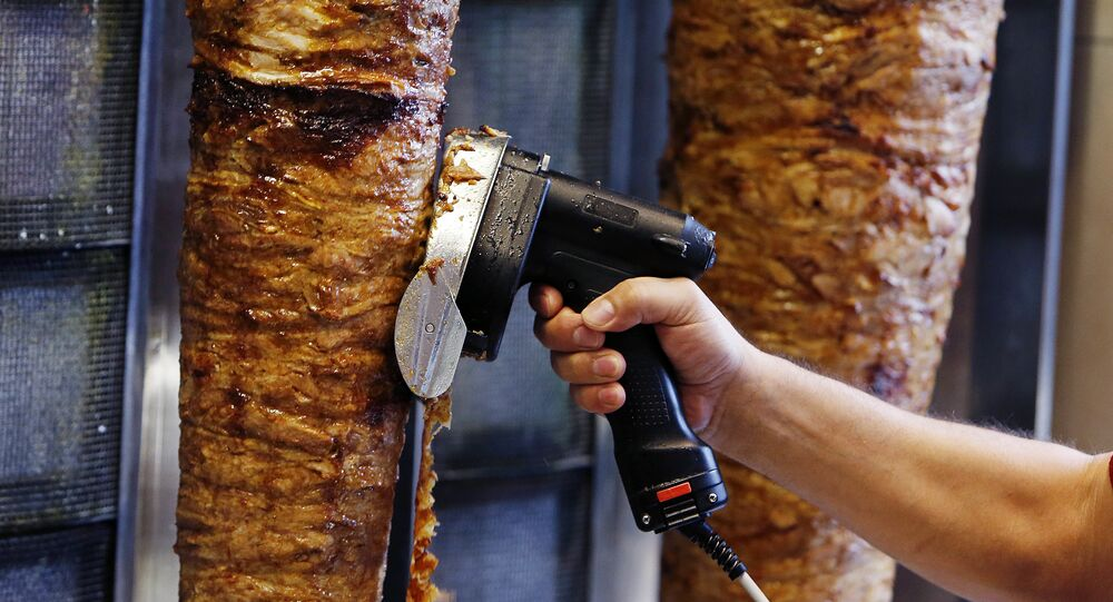 A man slices cuts of meat from a rotisserie Doner (photo used for illustration purpose)