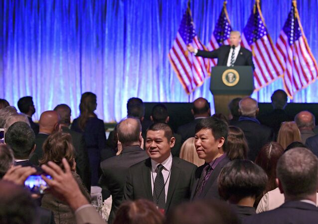 People in the audience have their photo taken as President Donald Trump speaks at a fundraiser