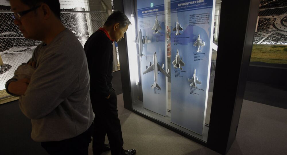 In this Sunday, Dec. 2, 2012 photo, a visitor, right, looks at model replicas of aircraft of the U.S. Air Force Kadena base on display at the Learning Exhibition Hall of Kadena in Kadena, Okinawa, southwestern Japan. For nearly 70 years, Okinawa has gotten more than its share of America's military - more jets rattling homes, more crimes rattling nerves. It's the only Japanese island invaded by U.S. land forces during World War II. It endured 27 years under U.S. administration, and it continues to host two-thirds of Japan's U.S. bases.
