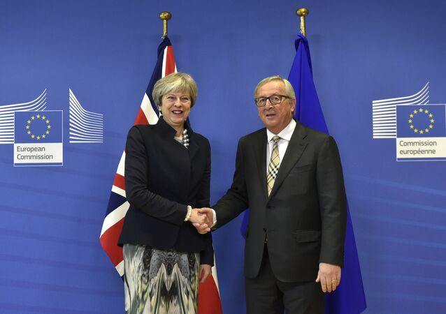 British Prime Minister Theresa May (L) shakes hands with European Commission chief Jean-Claude Juncker prior to a Brexit negotiation meeting on December 4, 2017 at the European Commission in Brussels