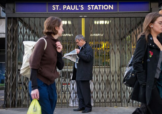 (File) A man stands outside the locked gates of St Paul's underground station in central London, on November 3, 2010