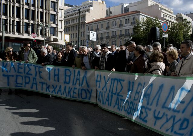Residents and Mayors of the island of Lesvos, Chios , and Samos hold a banner as they protest outside the Migration Ministry in central Athens, Tuesday, Dec. 5, 2017. The banner reads in Greek  island of Chios is not human warehouse