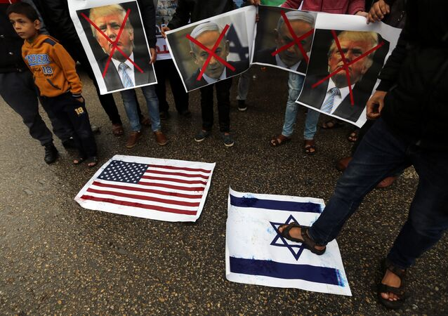 A Palestinian man steps on a representation of an Israeli flag as other demonstrators hold crossed out posters of US President Donald Trump and Israeli Prime Minister Benjamin Netanyahu during a protest against the U.S. intention to move its embassy to Jerusalem and to recognize the city of Jerusalem as the capital of Israel, in Rafah in the southern Gaza Strip December 6, 2017.