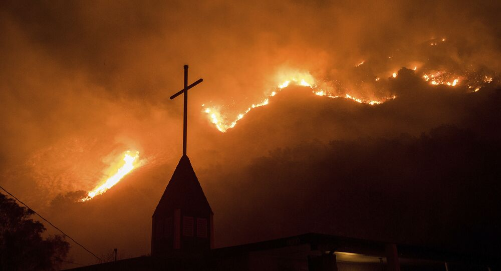 Flames from a wildfire advance down a hillside near the Springs of Life Church in Casitas Springs, Calif., on Tuesday, Dec. 5, 2017.