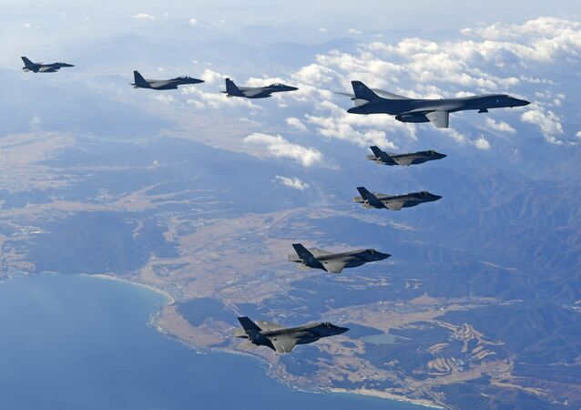 In this photo provided by South Korea Defense Ministry, U.S. Air Force B-1B bomber, right top, flies over the Korean Peninsula with South Korean fighter jets and U.S. fighter jets during the combined aerial exercise, South Korea, Wednesday, Dec. 6, 2017