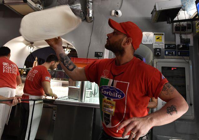 Neapolitan pizza makers prepare pizzas in a bottega on December 6, 2017 in Naples
