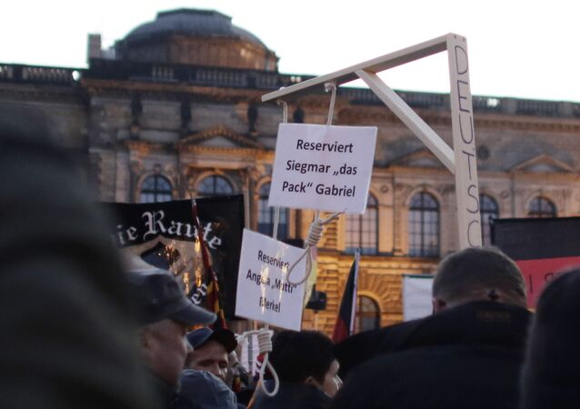 In this Oct. 12, 2015 photo a demonstrator carries a mock gallows with two hangman's nooses, marked Reserved for Angela Merkel and Reserved for Sigmar Gabriel, her deputy, during a demonstration of PEGIDA (Patriotic Europeans against the Islamization of the West) in Dresden, Germany