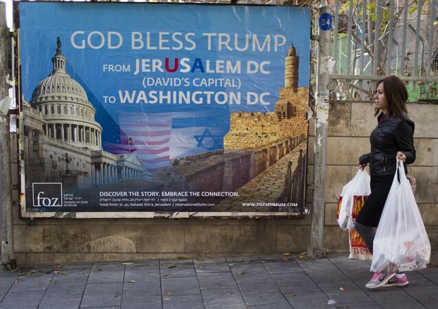 A woman walks past a poster praising U.S. President Donald Trump's recognition of Jerusalem as Israel's capital, in Jerusalem, Thursday, Dec. 7, 2017
