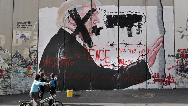 Palestinian children look at vandalised graffiti depicting US President Donald Trump and slogans against US Vice President Mike Pence painted on Israel's controversial separation barrier in the West Bank city of Bethlehem during clashes with Palestinian protestors near an Israeli checkpoint on December 7, 2017 - Sputnik International
