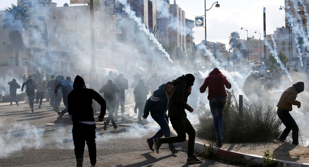 Palestinian protesters run from tear gas fired by Israeli troops during clashes at a protest against U.S. President Donald Trump's decision to recognize Jerusalem as the capital of Israel, near the Jewish settlement of Beit El, near the West Bank city of Ramallah December 7, 2017