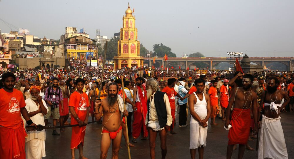 Indian Hindu holy men wait for their sect leader for holy dip on the second shahi snan or royal bath in the river Godavari during the ongoing Kumbh Mela, or Pitcher Festival, in Nasik, India, Sunday Sept. 13, 2015