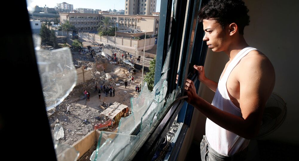 A Palestinian man looks out of his apartment that was damaged in an Israeli airstrike on a nearby militant target in the northern Gaza Strip December 9, 2017