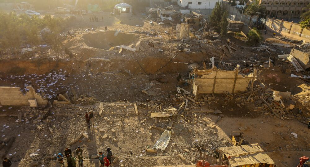 Palestinians look at the damage at a Hamas military facility early on December 9, 2017, in the aftermath of an Israeli air strike in Beit Lahia, in the northern Gaza Strip