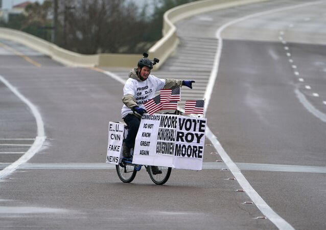 A man rides his bike with signs of support for Alabama Republican senatorial candidate Roy Moore around a venue that will host U.S. President Donald Trump later in the day in Pensacola, Florida, U.S., December 8, 2017
