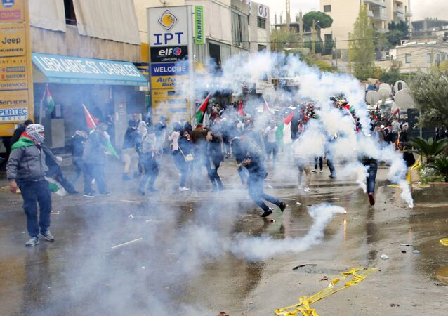 Protesters take cover from tear gas fired by riot police during a demonstration in front of the U.S. embassy in Aukar, east of Beirut, Lebanon, Sunday, Dec. 10, 2017