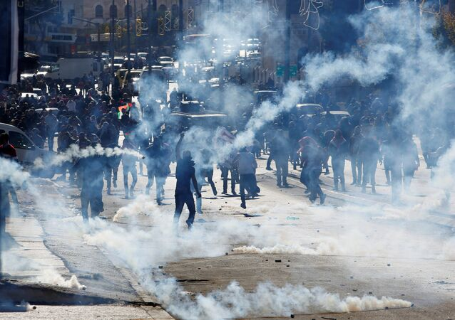 Palestinian demonstrators react to tear gas fired by Israeli troops during clashes at a protest against U.S. President Donald Trump's decision to recognize Jerusalem as the capital of Israel, in the West Bank city of Bethlehem December 9, 2017