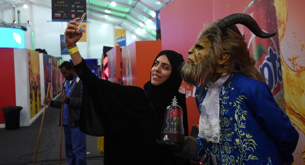 A Saudi woman uses her cell phone to take a selfie photograph with a cosplayer dressed as the Beast from Disney's 2017 live-action Beauty and the Beast film, as they attend the first ever Comic-Con Arabia event held in the capital Riyadh