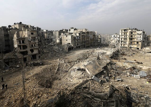 In this picture taken Friday, Jan. 20, 2017 from the balcony of the Abdul-Hamid Khatib home, people walk through mounds of rubble which used to be high rise apartment buildings in the once rebel-held Ansari neighborhood in the eastern Aleppo, Syria