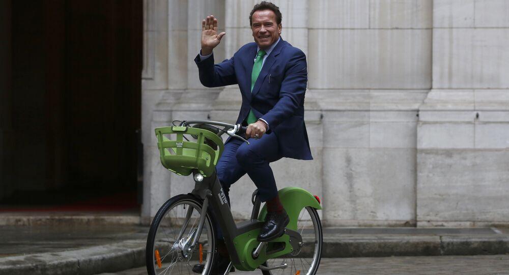 Arnold Schwarzenegger arrives on bicycle to meet Paris mayor Anne Hdalgo, Monday Dec. 11, 2017 in Paris