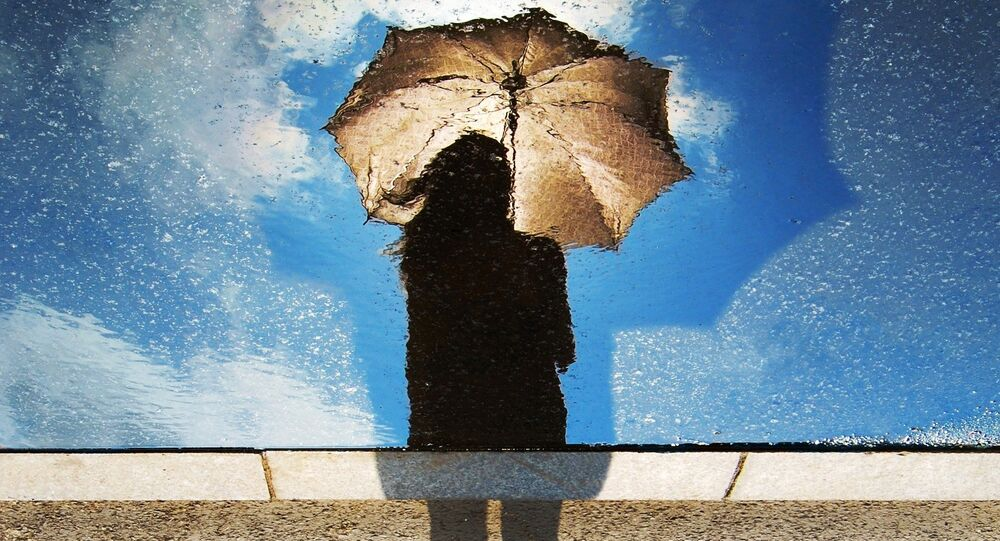 A silhouette of a woman holding an umbrella