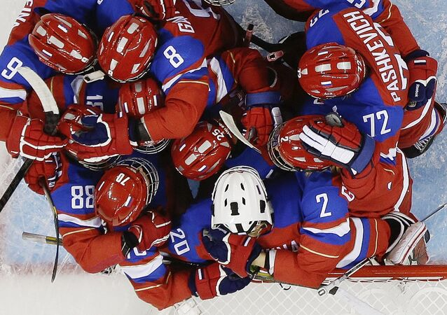 Members of Team Russia hug after defeating Japan 6-3 during the 2014 Winter Olympics women's ice hockey game at Shayba Arena Sunday, Feb. 16, 2014, in Sochi, Russia