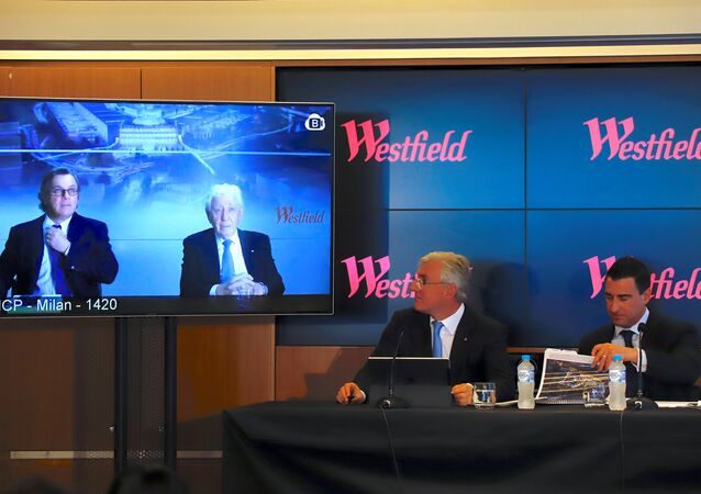 Westfield Chairman and co-founder Frank Lowy appears with his son Peter on a screen via video-link, as his other son Steven Lowy sits with Elliot Rusanow, Chief Financial Officer of Westfield, during a media conference in Sydney, Australia, December 12, 2017.