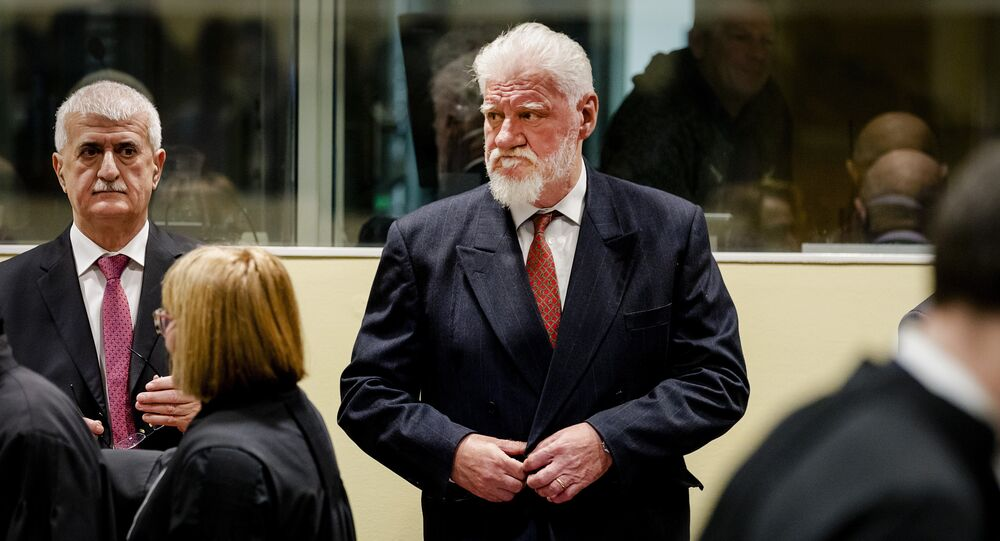 Slobodan Praljak, center, enters the Yugoslav War Crimes Tribunal in The Hague, Netherlands, Wednesday, Nov. 29, 2017, to hear the verdict in the appeals case