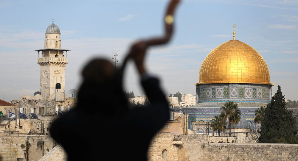 A man is silhouetted while he blows a Shofar, a ram horn, as the Dome of the Rock (R), located in Jerusalem's Old City on the compound known to Muslims as Noble Sanctuary and to Jews as Temple Mount, is seen in the background December 10, 2017