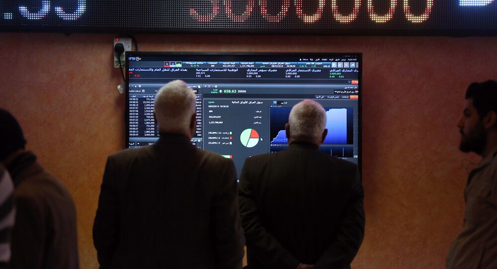 In this Monday, Feb. 8, 2016 photo, Iraqi stock traders watch the sales screen at the Baghdad Stock Exchange, in Baghdad, Iraq. Plunging oil prices have pitched Iraq into a severe financial crisis as it struggles to combat the Islamic State group, play host to millions of refugees and rebuild cities and towns ravaged by war